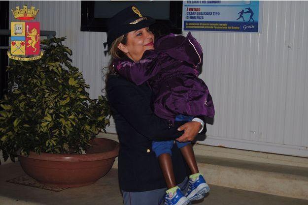 La petite Oumoh dans les bras de l'inspectrice Maria Volpe, qui l'a pris en charge depuis son arrivée à Lampedusa.