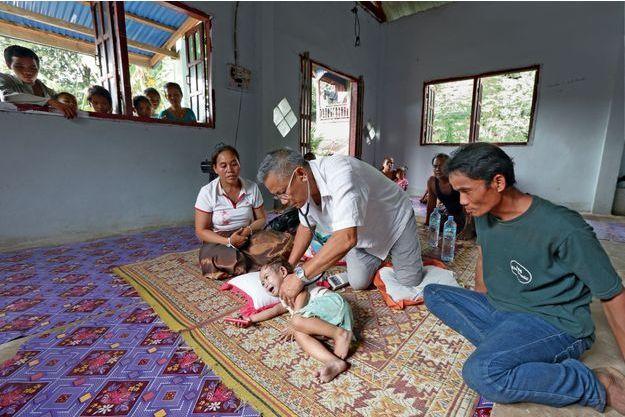 Alphonse Pluquailec, médecin franco-laotien, ausculte Do, 2ans et demi,  sous le regard attentif de ses parents, dans leur maison de Champassak dans le sud du Laos.