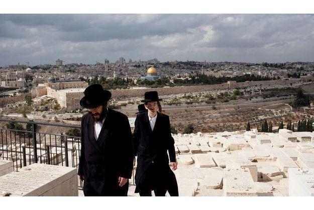 Le mont des Oliviers. Des Juifs orthodoxes sont venus se recueillir sur les tombes de rabbins. Depuis le cimetière, ils ont vue sur les remparts de la vieille ville, la mosquée Al-Aqsa, à gauche, le dôme bleu du Saint-Sépulcre et le dôme doré du Rocher. Au fond, les gratte-ciel de Jérusalem-Ouest.