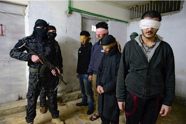 Dans le sous-sol d'un ex-commissariat de Til Koçer, lundi 15décembre, quatreislamistes surveillés par des Kurdes qui restent masqués, pour éviter d'être identifiés par Daech.