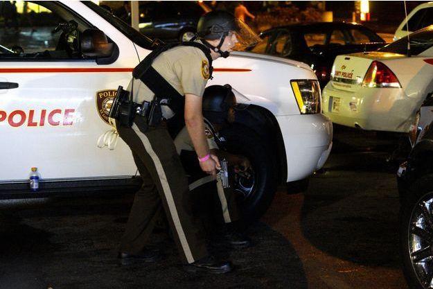 Un policier en planque à Ferguson alors que des coups de feu se sont fait entendre dimanche soir.