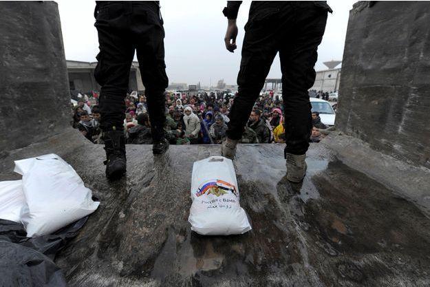 Des soldats russes distribuent des rations de nourriture à des habitants qui ont fui Alep-Est.