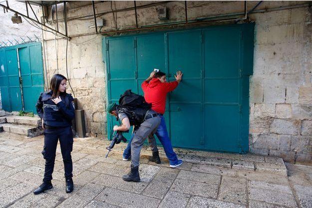 Un policier israélien fouille un palestinien après l'attaque du garde-frontière.