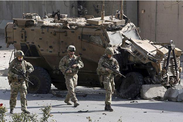Des soldats de l'Otan marchent à côté d'un véhicule blindé à Kaboul, en octobre 2015.