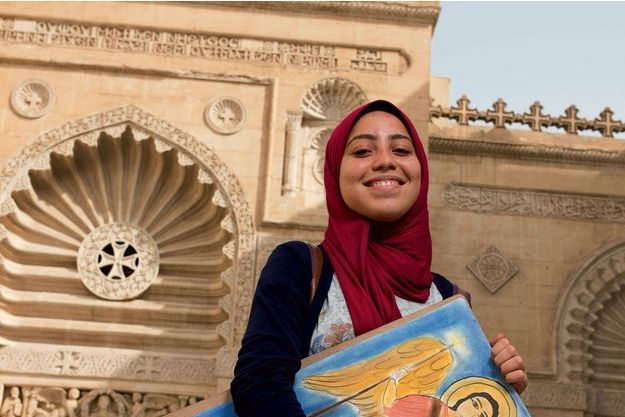 Yasmine, étudiante musulmane en arts appliqués, avec le dessin de l'archange Michel qu'elle vient de réaliser. La façade du musée mêle des croix et des calligraphies typiques de l'art islamique.