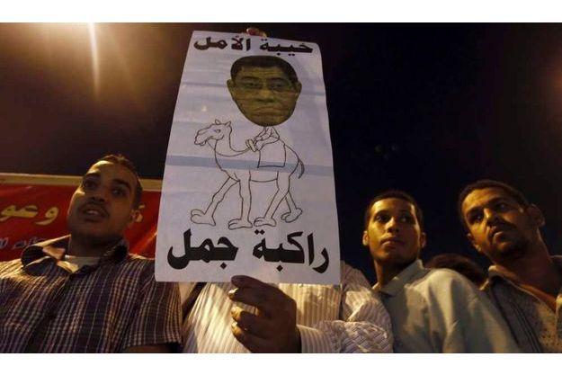 Des manifestants brandissent un dessin du procureur général Abdel Meguid Mahmoud et d'un chameau, pour dénoncer le pouvoir qu'ont encore certains caciques de l'ère Moubarak.