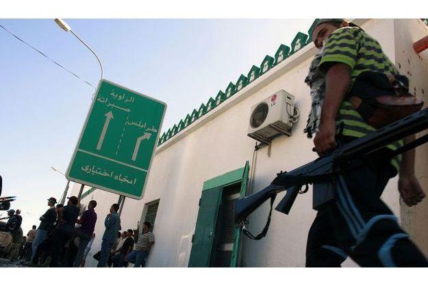 Des combattants insurgés dans Zawyiah. Sur le panneau, la direction de Tripoli.