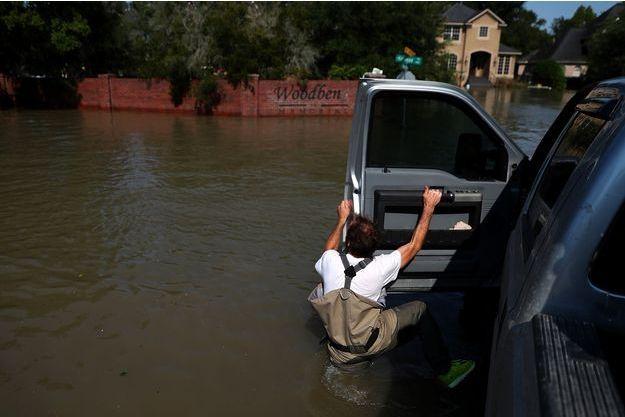 Un homme tente de monter dans sa voiture dans les rues inondées de Houston.