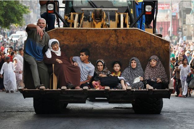 Dimanche 20 juillet, des habitants de Chajaya profitent d'une trêve humanitaire de deux heures pour quitter leur quartier à bord d'une pelleteuse.