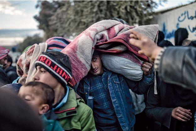 Sur la tête de cet homme, les maigres possessions qu'il a emportées dans sa fuite. Ces réfugiés venus d'Alep tentent de passer en Turquie, le 5 février.