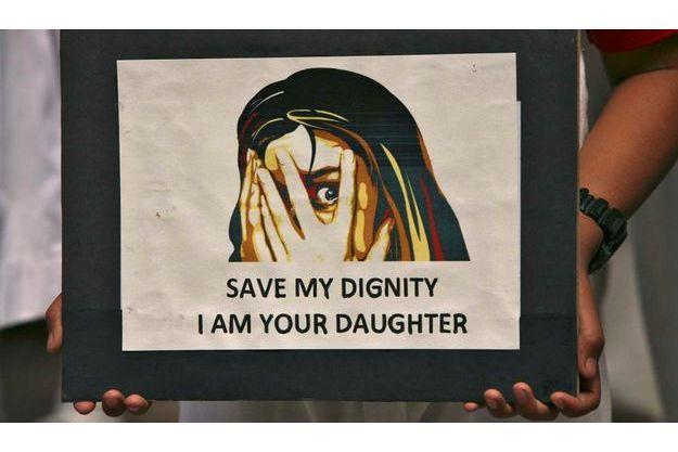 """""""Sauve ma dignité, je suis ta fille"""", dit la pancarte, tenue par une jeune indienne lors d'une manifestation."""