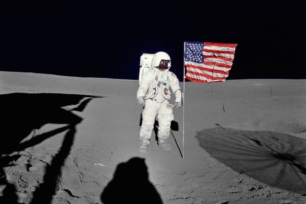 Edgar Mitchell à côté du drapeau américain pendant la mission Apollo 14 en 1971.