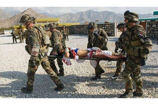 Des soldats français évacuent un blessé civil après que des insurgés talibans ont tiré trois roquettes sur un marché très fréquenté de Tagab, en novembre 2009.