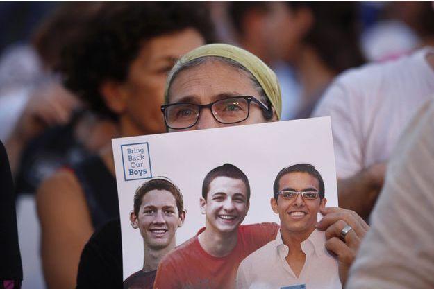 Une femme porte les photos des trois jeunes Israéliens pendant une mobilisation à Tel Aviv, en juin dernier.