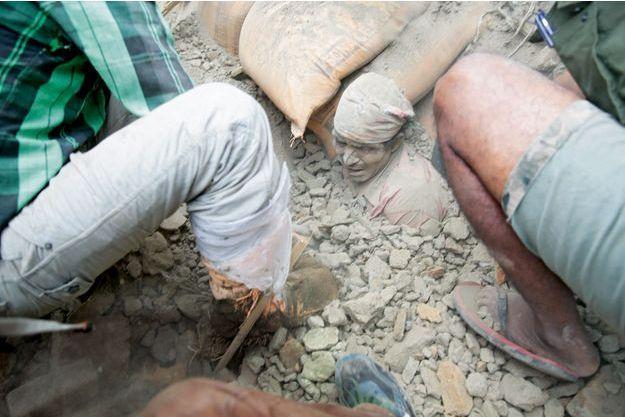 A mains nues, des habitants dégagent un survivant des décombres. Il faudra encore de longues minutes pour qu'il se mette à marcher.