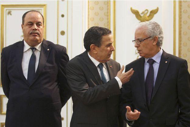 Le ministre tunisien de la Défense Farhat Horchani (au centre) parle avec le ministre de la Justice Mohamed Salah Ben Aissa, au côté du ministre de l'Intérieur Mohamed Gharsalli, lors d'un conseil ministériel d'urgence à Tunis.