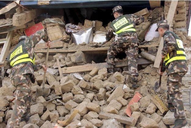 Des secouristes tentent de chercher des survivants dans les décombres.