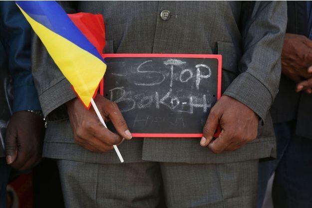 Un homme regarde partir les troupes tchadiennes vers le Cameroun avec un écriteau sur lequel on peut lire «Arrêtez Boko Haram», à Ndjamena.
