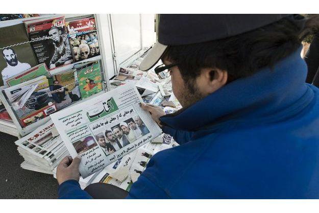Un homme lit la Une d'un journal devant un kiosque à journaux de Téhéran, dimanche.