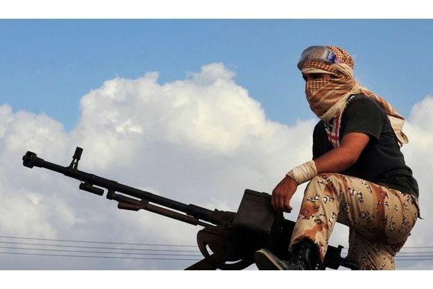 Un combattant prend son poste derrière un canon antiaérien à Syrte, mardi.