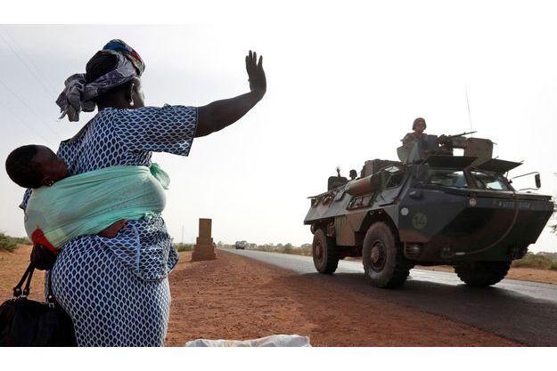 Une femme salue un blindé français à Diabaly.