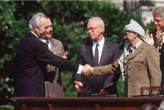 Shimon Peres serre la main de Yasser Arafat sous les yeux d'Yitzhak Rabin, en 1993, après la signature des accords d'Oslo.