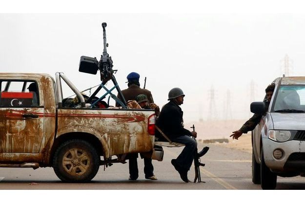 Des rebelles assis à un check-point, le long de la route Benghazi-Ajdabiyah, près de la ville d'Ajdabiyah.