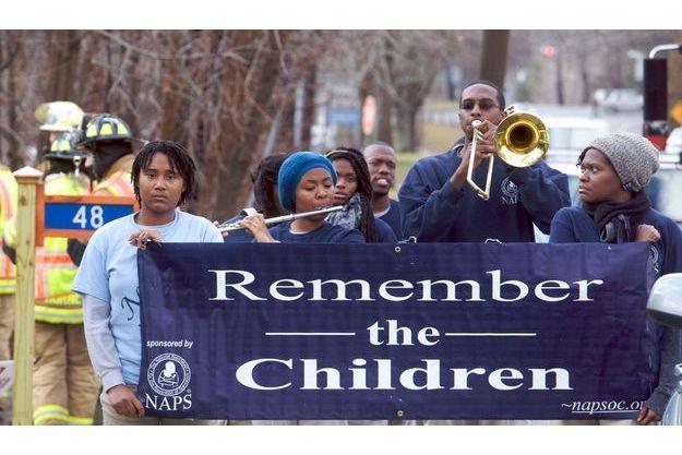 """""""Souvenez-vous des enfants"""" lit-on sur cette pancarte brandie lors des funérailles de Rachel Marie D'Avino, l'une des petites victimes de la tuerie."""
