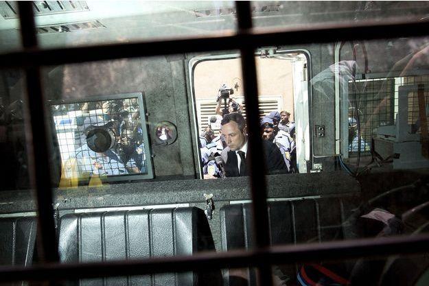 Oscar Pistorius montant dans le véhicule qui l'a conduit à la prison de Pretoria, mardi 21 octobre.