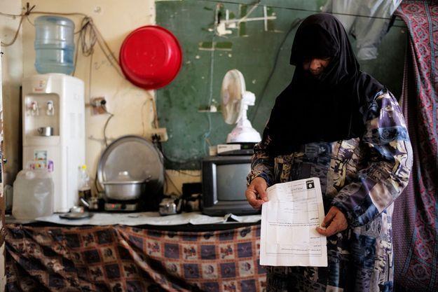 Badrieh Ali Hussein tenant dans les mains le certificat d'exécution de sa fille Fatma par Daech