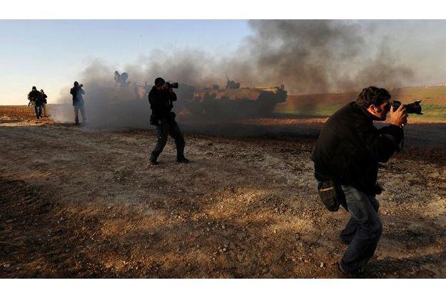 En avril 2009, des reporters photographient les troupes israéliennes à l'entrée de Gaza.