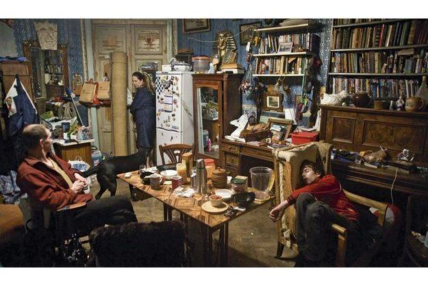 Scène de vie ordinaire dans une kommunalka. Une famille vit dans une pièce qui fait salon-chambre- bibliothèque- salle-à-manger.