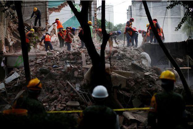 Des sauveteurs cherchent des victimes coincées sous les décombres à Mexico.