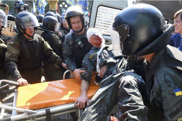 Des membres de la garde nationale portent l'un des leurs, blessé lundi, à Kiev.