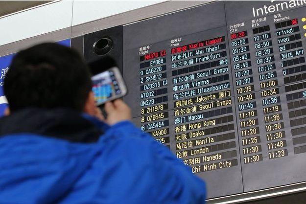 Angoisse à l'aéroport de Pékin, où était attendu le vol MH370, en rouge sur le tableau.