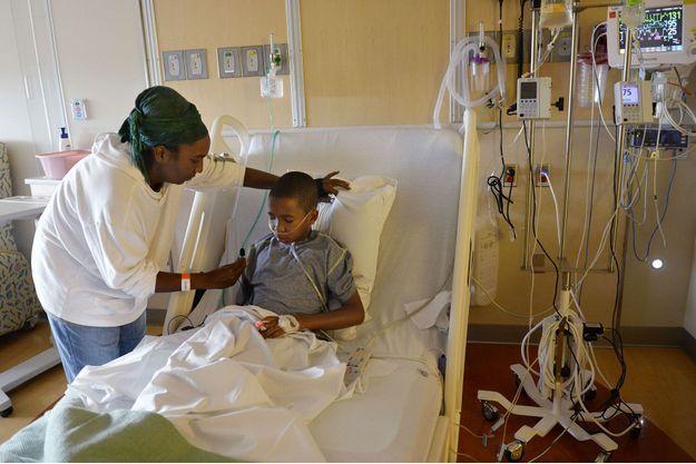 Une femme aide son fils touché par le virus, hospitalisé à Denver, en septembre dernier.