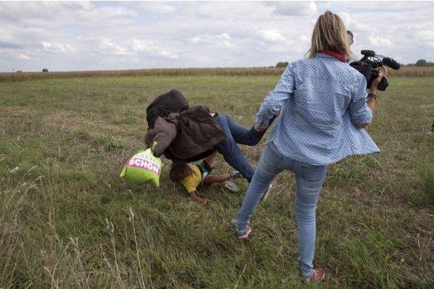 Petra Laszlo, de dos, fait un croche-pied à un réfugié le 8 septembre 2015.
