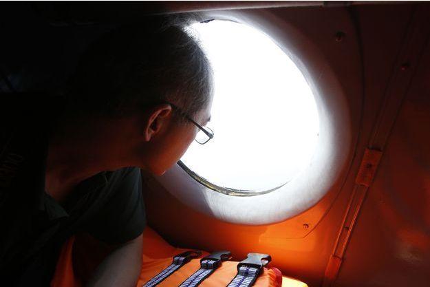 Un journaliste chinois regarde à travers la fenêtre d'un avion utilisé pour les recherches du vol MH370.