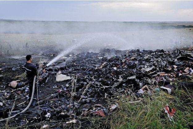 Grabovo, le 17juillet. A quelques kilomètres de la frontière russe, les premiers sauveteurs arrivés sur les lieux du drame éteignent les flammes de l'incendie du Boeing777.