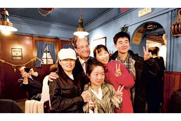 Vendredi soir, au restaurant André, François Hollande est reconnu par des touristes chinois, qui insistent pour poser avec lui en faisant  le « V » de la victoire.