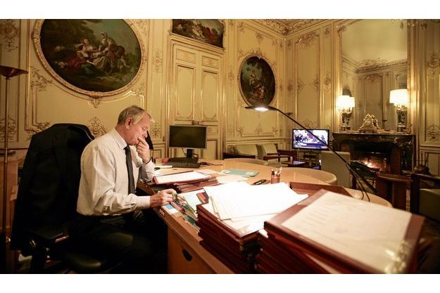 Vendredi 16novembre, à 20heures. Une main sur le parapheur, un œil sur le JT, le Premier ministre est encore au travail.