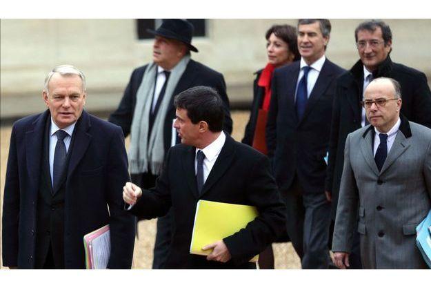 Jean-Marc Ayrault, Manuel Valls et Bernard Cazeneuve à la sortie du ministère de l'Intérieur, jeudi.