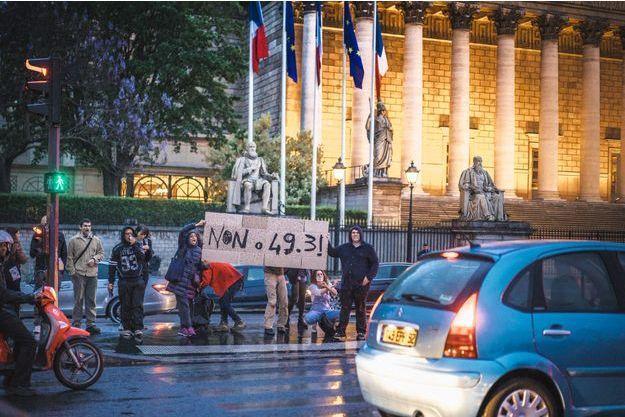 Lundi soir, des manifestants dénoncent l'éventuel recours au 49-3 devant l'Assemblée nationale, à Paris.