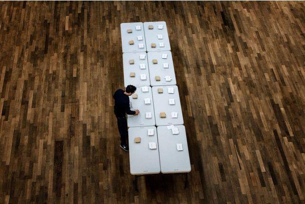 Mise en place des bulletins dans un bureau de vote à Lyon, le 23 avril.