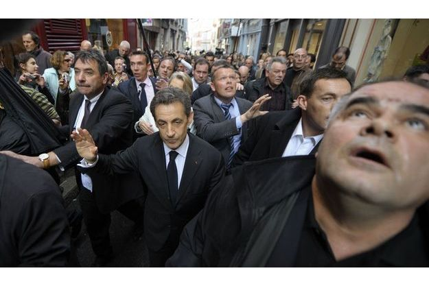 Nicolas Sarkozy, jeudi, dans le centre de Bayonne, entouré de policiers en civil.