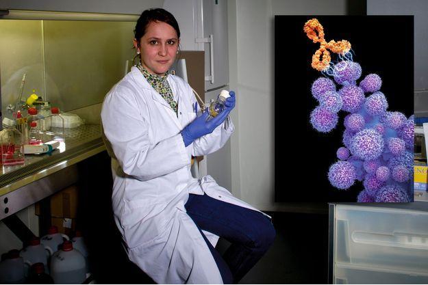 Le Dr Aurélie Juhem. En médaillon: anticorps monoclonal cetuximab (en orange) attaquant des cellules cancéreuses (en violet). Cetuximab est utilisé en chimio pour traiter le cancer.