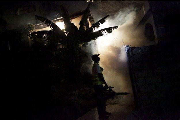 Un employé du gouvernement lance des produits contre les moustiques en Haïti.