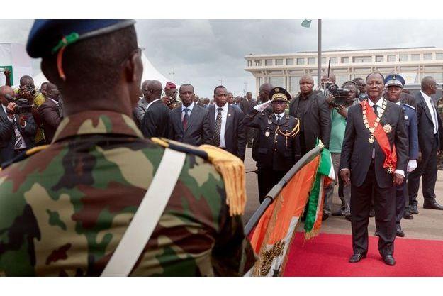 Alassane Ouattara, assisté de son aide de camp (arrière-plan, en uniforme bleu)  et de Soumaïla Bakayoko, l'ancien chef des forces rebelles (à g.), passe en  revue les troupes qui lui font allégeance en lui présentant le drapeau national.