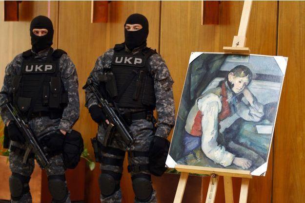 """Deux policiers d'élite serbes surveillent le """"Garçon au gilet rouge"""" de Paul Cézanne, en 2012. La toile avait été volée lors d'un braquage dans une galerie suisse quatre ans plus tôt."""