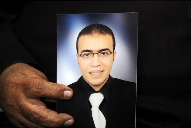 Reda al-Hamahmy, le père du suspect de l'attaque au Carrousel du Louvre, tenant une photo de son fils.